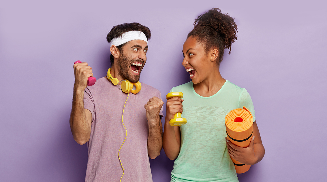 Be strong and healthy. Emotional diverse woman and man scream from joy, look at each other, stand with sport equipment, train muscles with small dumbbells, carry fitness mat, have workout in gym